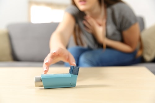 woman reaches for asthma inhaler